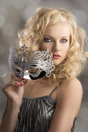femme masqu�e: jolie fille blonde aux cheveux boucl�s prend un masque d'argent, son corps est tourn� de trois quarts � gauche, elle regarde dans la lentille et prend le masque avec la main droite