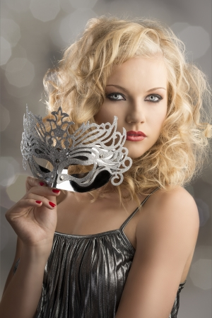 pretty blonde girl with curly hair takes one silver mask, her body is turned of three quarters at left , she looks in to the lens and takes the mask with right hand Stock Photo