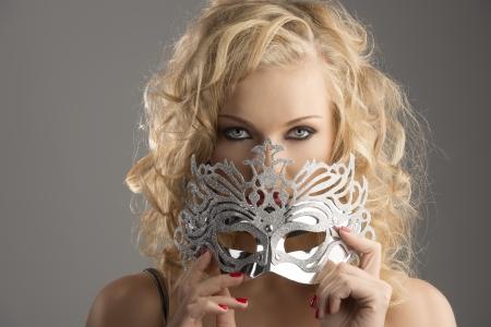antifaz de carnaval: linda chica rubia con el pelo rizado tiene una máscara de plata, que se encuentra en frente de la cámara, toma la máscara sobre la boca y mira a la lente