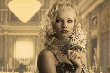 mascara de carnaval: linda chica rubia con el pelo rizado tiene una máscara de plata, ella se gira de tres cuartos a la izquierda, se ve a la derecha y toma la máscara con la mano derecha