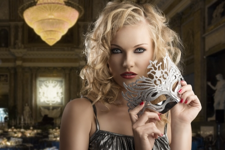 pretty blonde girl with curly hair takes one silver mask, she looks in to the lens and takes the mask with both hands near the chin Stock Photo