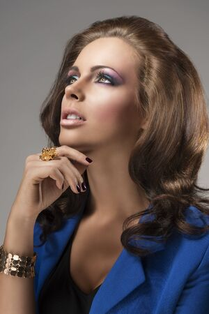 sexy mature women: pretty girl with blue jacket and fluffy hair, she is turned of three quarters at right, looks up and her right hand is near the chin