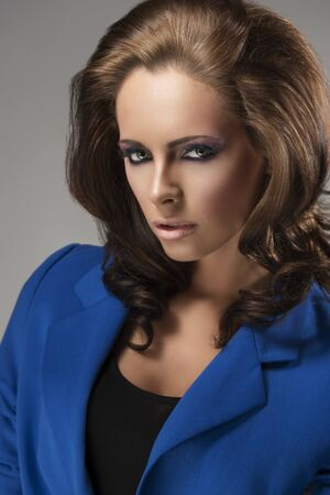 sexy mature women: pretty girl with blue jacket and fluffy hair, she is turned of three quarters at right and looks in to the lens with sensual expression