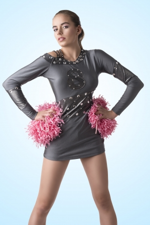 pretty cheerleader with silver uniform and pink pompom, she looks in to the lens and takes the pompom with both hands near the hips photo