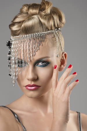 portrait of pretty girl with the elegant hair style and indian decoration on the head, she looks in to the lens and has the right hand near the face Stock Photo - 16479674