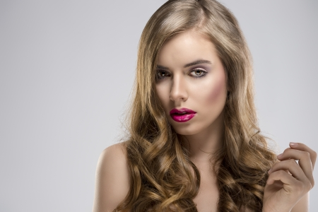flowing hair: pretty girl with flowing wavy hair and purple make-up, she is turned of three quarters at right and looks in to the lens Stock Photo