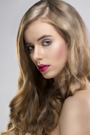 pretty girl with flowing wavy hair and purple make-up, she is turned at right and looks in to the lens photo