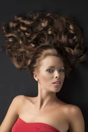 flowing hair: pretty girl with brown long curly hair lying on the black floor, her face is turned of three quarters and looks in to the lens Stock Photo