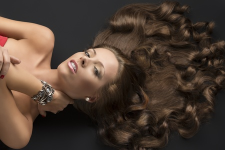 flowing hair: pretty girl with brown long curly hair lying on the black floor, she looks in to the lens and her left hand is on the neck