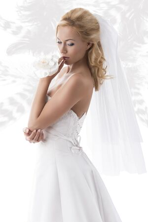 bridal veil: beautiful blonde girl with white wedding dress, she looks down at left and has the left hand near the lips Stock Photo