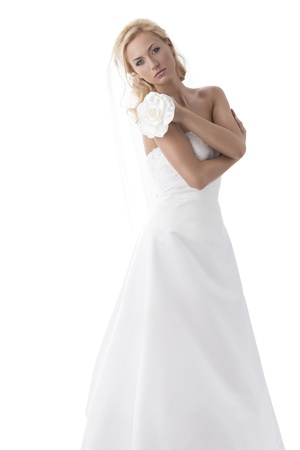 sexy bride: beautiful blonde girl with white wedding dress, she looks in to the lens with sensual expression and the left hand on the right shoulder