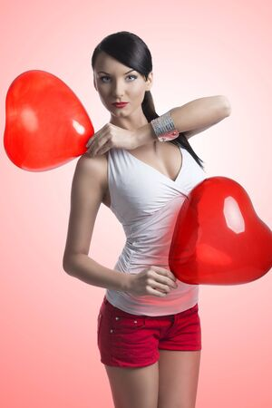 pretty brunette with shorts and two heart shaped balloons in the hands and takes on of those on the right shoulder photo
