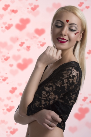 heart under: prety blonde girl with sexy clothing and heart shaped decoration on the face, she smiles and looks down at left, her left hand is under the chin