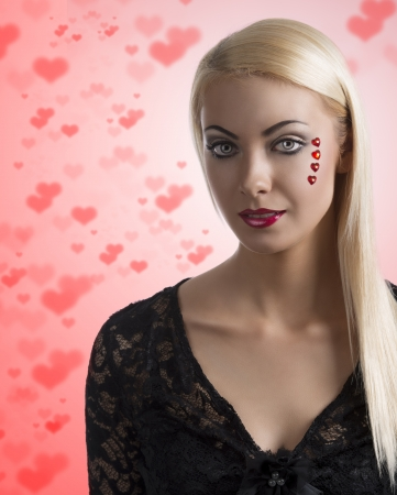 prety: prety blonde girl with sexy clothing and heart shaped decoration on the face, she looks in to the lens