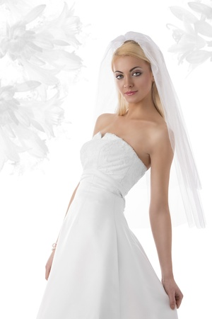 wedding veil: pretty girl with white wedding dress and veil, she is turned of three quarters at right and looks in to the lens Stock Photo