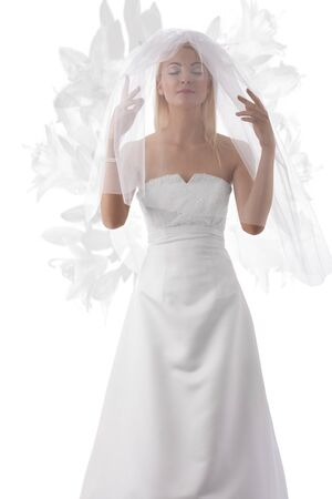 wedding veil: pretty blonde bride with white veil con the face, her hands are under the veil and her eyes are closed