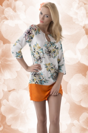 clothing model: pretty blonde girl with flower in the hair clothing dress with floral pattern, she looks in to the lens with sensual expression and has the left hand on the left hip Stock Photo