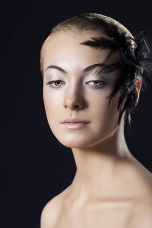 black feathered: beauty portrait of blonde girl with black feathered accessory on the face