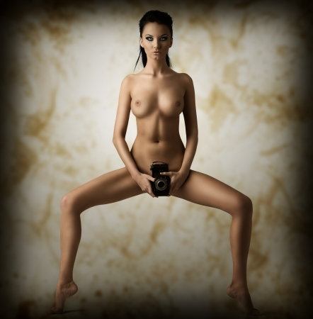 girl sexy nude: pretty naked brunette takes vintage camera on her pubis with both hands, she is in front of the camera and looks in to the lens Stock Photo