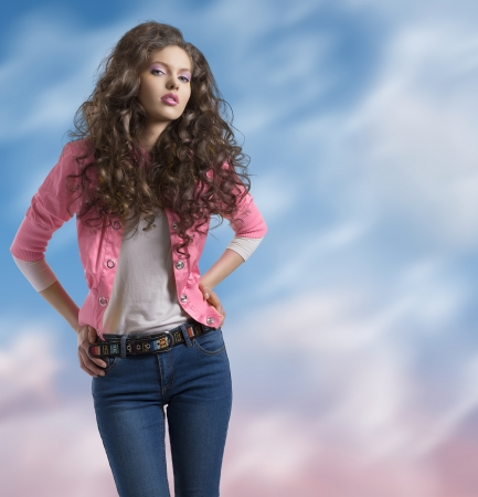 pretty brunette with wavy and volume hair wears blue jeans and jellow jacket, she looks in to the lens and her hands are on the hips Stock Photo