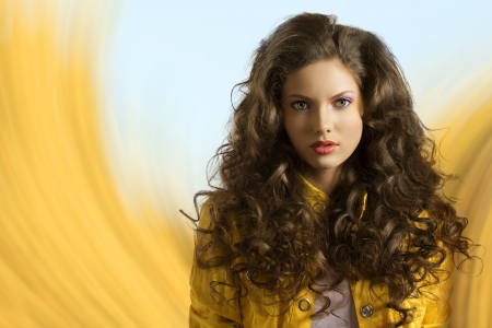 pretty brunette with wavy and volume hair wears blue jeans and jellow jacket, her hairs are on the shoulders and she looks in to the lens photo