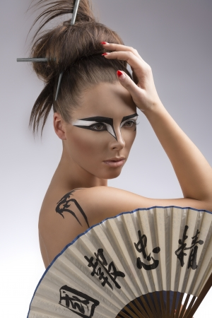 sexy brunette with japan make-up and asian fan, she is turned of three quarters at left and her right hand is on the head photo