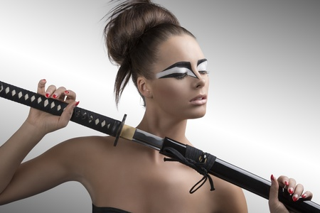 pretty brunette with japan make-up japan sword, her face is turned at left and she takes the sword with both hands photo