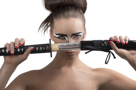 pretty brunette with japan make-up japan sword, she is in front of the face and takes the sword in front of the face  Stock Photo - 18501453