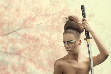 pretty brunette with japan make-up japan sword, she looks at right and takes the sword with left hand Stock Photo - 18501455