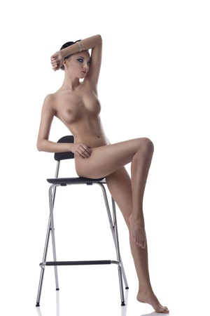 nude brunette sitting on a chair Stock Photo