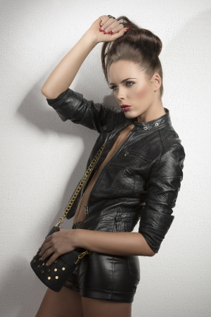 very young sexy brunette with leather jacket, shorts and bag with hair style near a wall