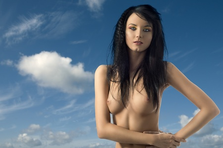 topless brunette: cute brunette with long hair in topless and blue sky with some clouds on the background