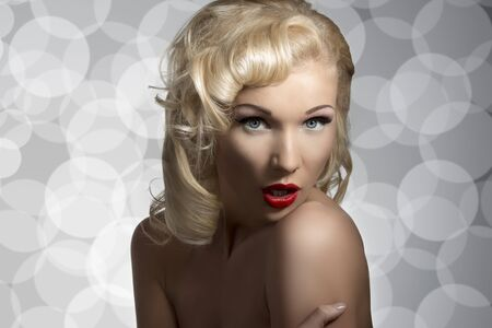 nude blonde girl: portrait of blonde surprised girl with retro make-up and hairstyle, nude shoulders looks in camera on gray background