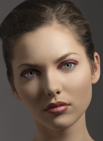 close-up portrait of beauty girl with green eyes, red glossy make-up and brown hair on gray background