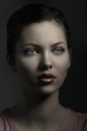pelo castaño claro: joven y bella mujer cerca de retrato con rojo maquillaje, pelo castaño y ojos verdes en luz oscura
