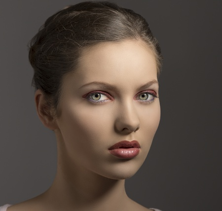 young sensual lady with purple make-up, perfect skin, brown hair looking in camera on gray background photo