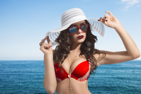 portrait of pretty girl with brown wavy hair, red sexy bikini, white summer hat and sunglasses near the sea