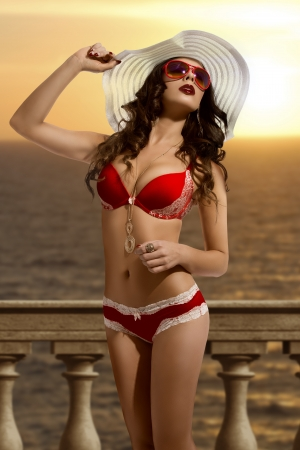 lingerie model: beautiful brunette sunbathing with red bikini, sunglasses and white hat during sunset on the sea