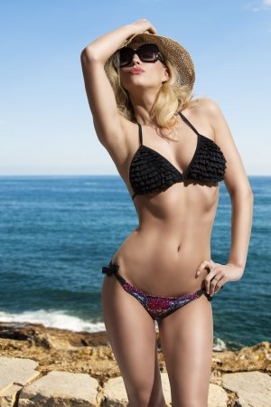 provocative blonde girl with sexy bikini, hat and sunglasses in summertime in sensuale pose with sea on background