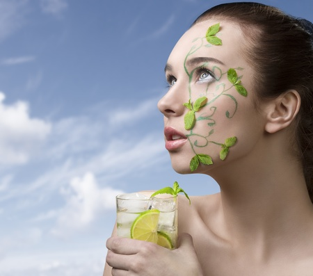 pretty girl with brown hair having creative green make-up with some mint leaves, naked shoulder and mojito cocktail  in the hand photo