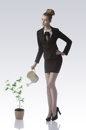 young blonde business woman with dark elegant suit watering one euro money plant with watering can photo