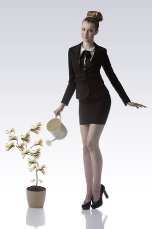 smiling blonde business woman with elegant dark suit and heels watering 50 euro money plant and looking in camera photo