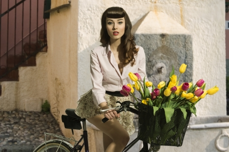 sensual brunette pin-up girl sitting on bicycle with some colorful tulips in the basket and wearing short skirt and pink shirt
