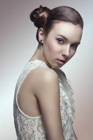 sensual young girl with brown hair tied in lateral chignon hairstyle looking in camera and wearing sexy lace shirt Stock Photo