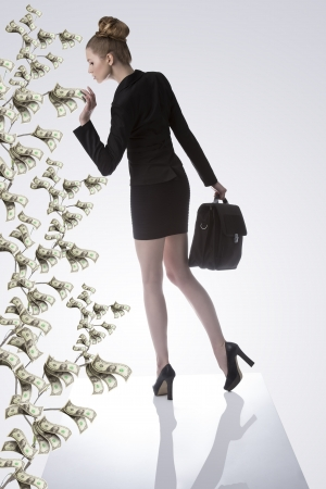 pretty business woman in full lenght wearing formal suit and keeping bag and taking a dollar from a money tree