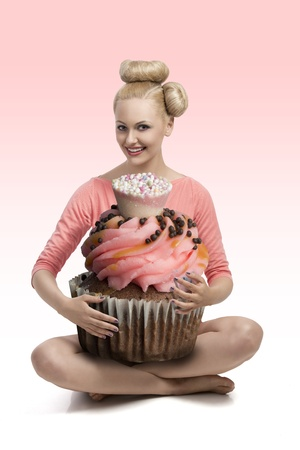 funny portrait of pretty blonde girl with creative hair-style and make-up taking colorful big cupcake in the arms photo