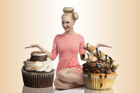 pretty blonde girl with colorful make-up and creative hair-style sitting on the floor and shows two big cupcakes Stock Photo - 20048418