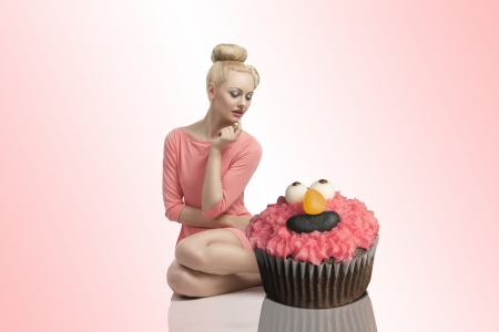 pretty blonde woman sitting near two big cupcakes with colorful make-up and creative hair-style Stock Photo - 20048410