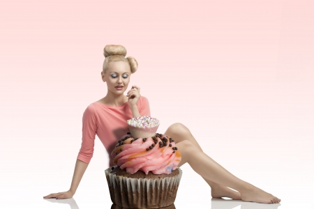 cute blonde woman sitting behind big cupcake with creative hair-style and colorful make-up photo