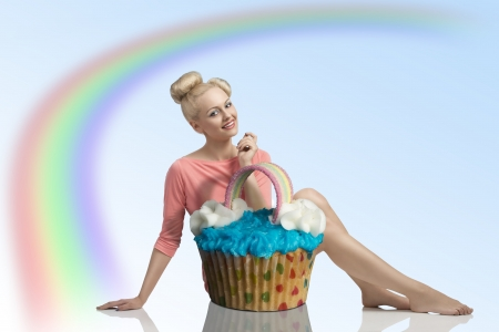 sexy food: smiling blonde girl with pink dress, color make-up and funny hair-style sitting behind big cupcak and looking in camera